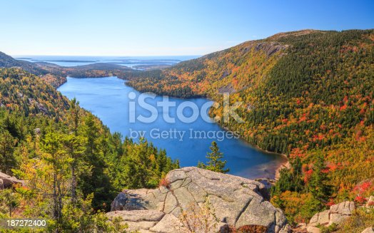 An aerial, stitched panoramic  view of Jordan Pond in Autumn from the top of South Bubble, looking east towards the Atlantic Ocean and the Cranberry Isles. Penobscot Mountain is in the mid-foreground on the right.