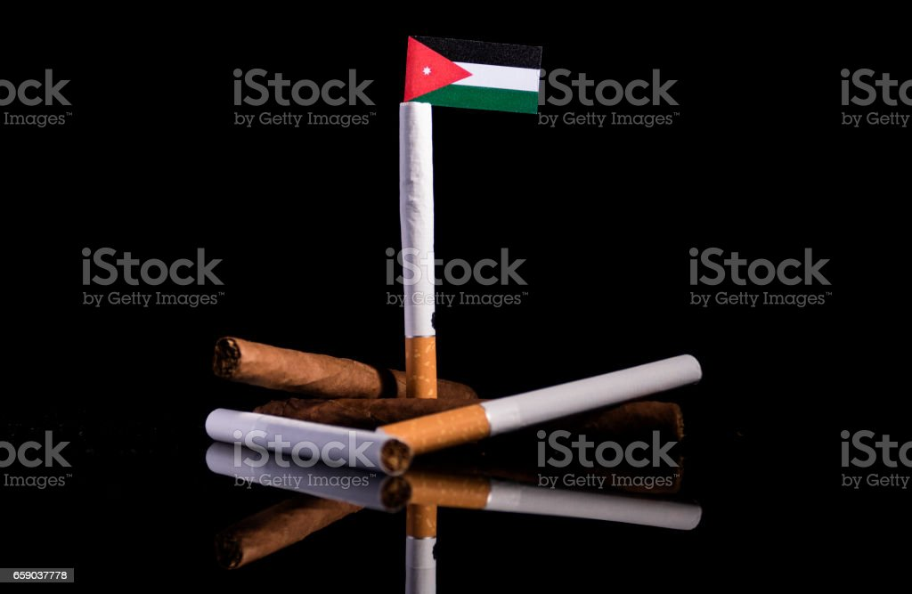 Jordanian flag with cigarettes and cigars. Tobacco Industry concept. royalty-free stock photo