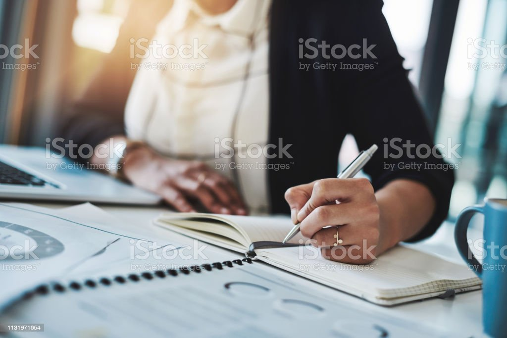 Jot it down and just do it Cropped shot of a businesswoman making notes at her desk in a modern office Adult Stock Photo