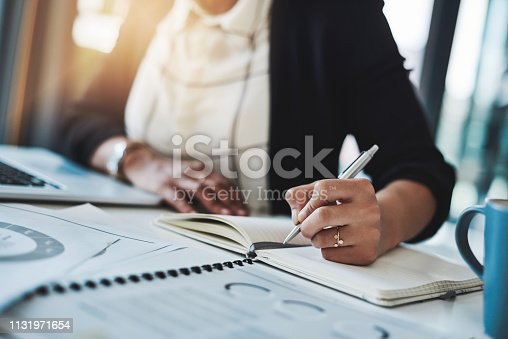 Cropped shot of a businesswoman making notes at her desk in a modern office