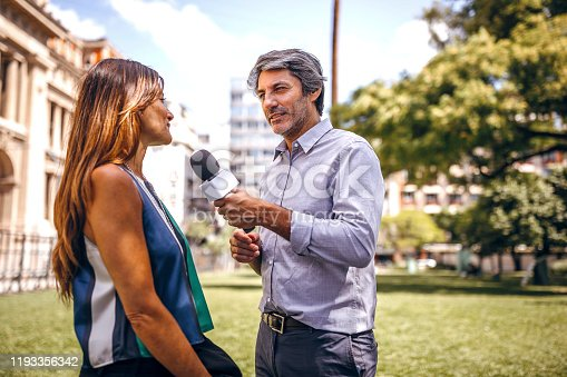 Man having interview for TV with attractive woman, asking a few questions on the street