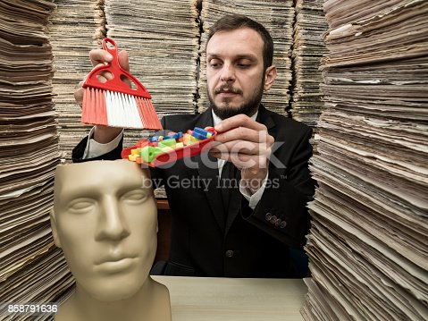 Mid adult man wearing a black suit and necktie filling mannequin brain with letters representing news and knowledge. He is using a dustpan. There are large amount of newspapers stacked on desk and on the background. The mannequin is placed on the left side of frame. Shot indoor with medium format camera.