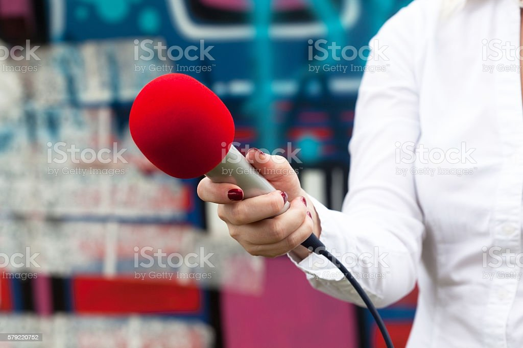 Journalist holding a microphone conducting an TV or radio interview stock photo