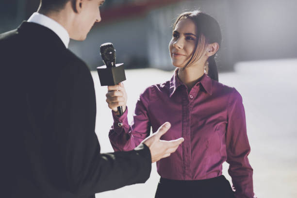 A journalist in a burgundy shirt smiling listens to the man's response stock photo