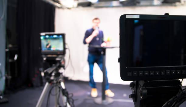 journaliste dans un studio de télévision parle dans un microphone, les caméras floues film - interview photos et images de collection