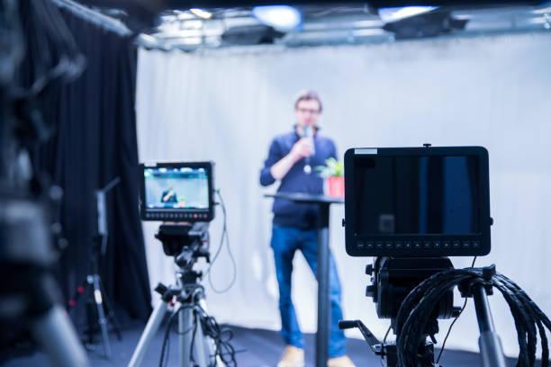 journalist in einem fernsehstudio spricht in ein mikrofon, verschwommene filmkameras - film oder fernsehvorführung stock-fotos und bilder