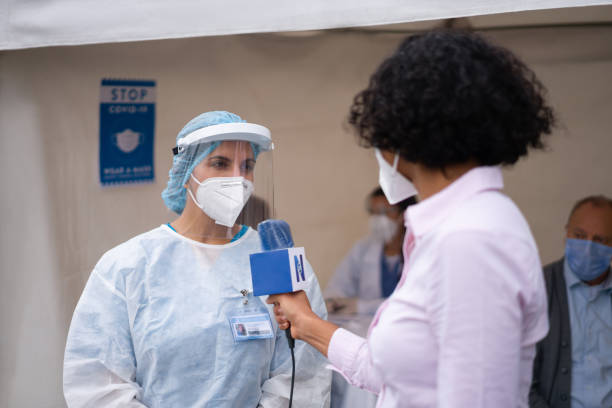 Journalist interviewing a healthcare worker working at a COVID-19 vaccination stand stock photo
