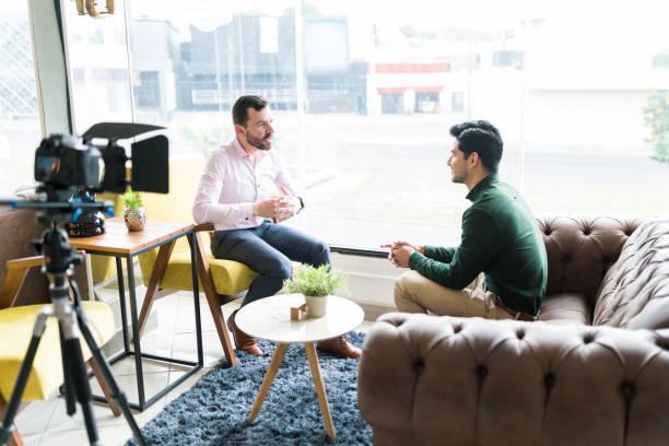 journaliste interviewant l'homme d'affaires dans le lieu de travail - interview photos et images de collection