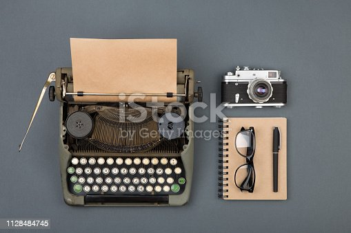 504606248 istock photo Journalist or private detective workplace - typewriter, camera, and other stuff 1128484745