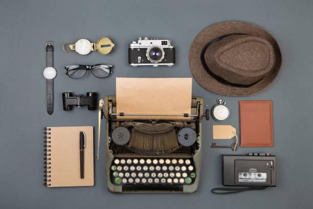 Jornalista ou detetive particular no local de trabalho - máquina de escrever, câmera, chapéu, gravador e outras coisas - foto de acervo