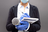 istock Journalist wearing protective gloves and face mask against coronavirus COVID-19 disease holding microphone writing notes during virus pandemic 1270825256