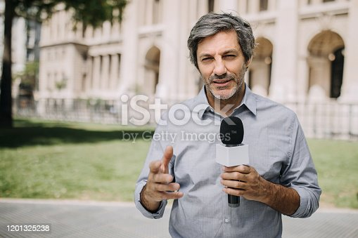 Journalist with microphone on the city streets