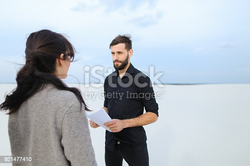 race driver meet with journalist female to tell about hobby, people shake hands at end of conversation. Lady with ponytail in white blouse beige skirt holding planchette talking with bearded male in black shirt trousers. Concept of collecting information for article, fashionable clothes or stylish man and woman outfits.
