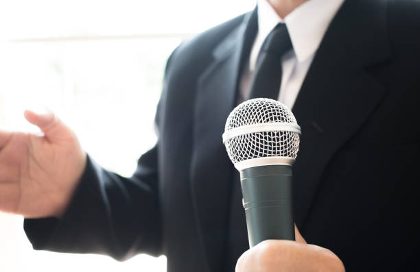 Journalists filing microphone interviewing to businessman. Smart Reporter taking interview and speech with microphone at presentation in conference, Business seminar concept stock photo