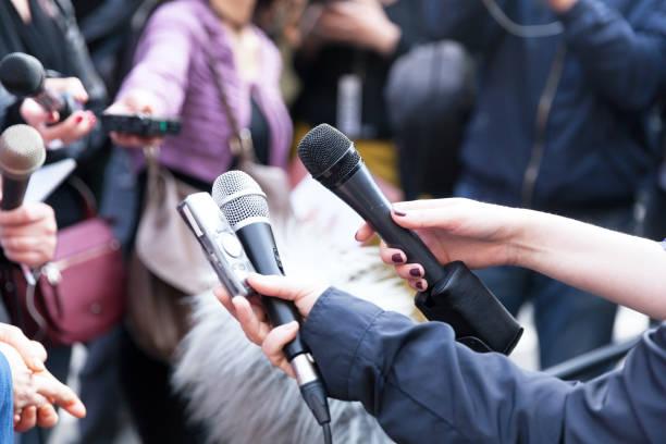 Journalisten halten Mikrofone bei Pressekonferenz – Foto