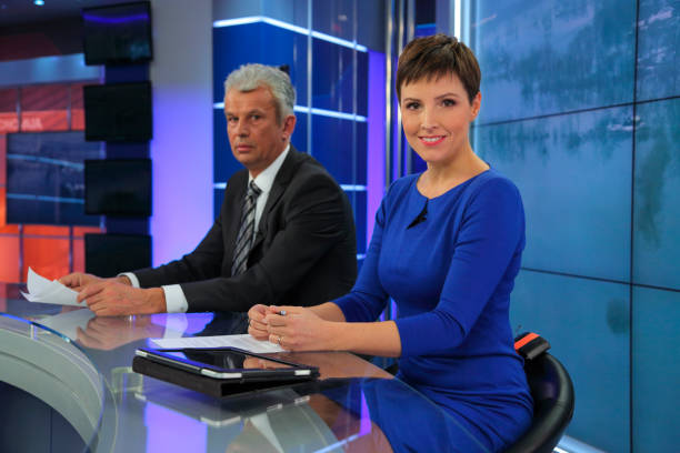 Journalists in a tv news studio Mature man and younger woman sitting at news desk in a tv recording studio. anchor stock pictures, royalty-free photos & images