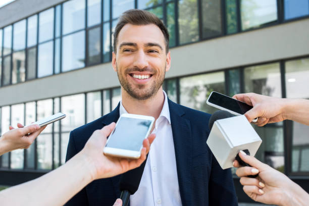 journalists interviewing smiling successful businessman with microphones and smartphones - dictaphone stock pictures, royalty-free photos & images