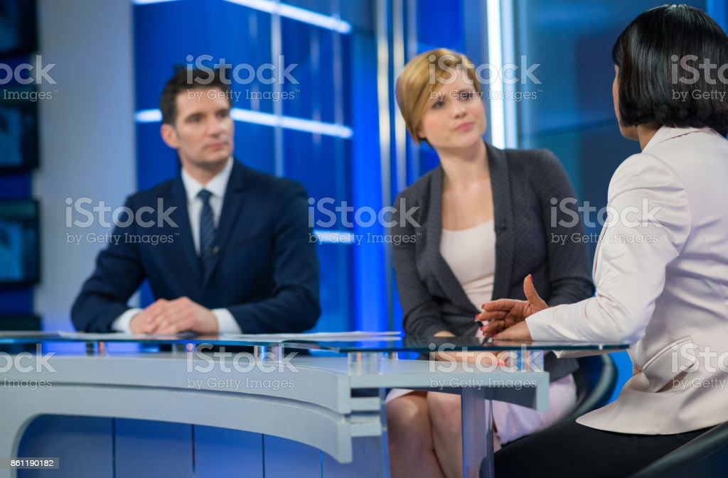 Journalists Sitting With Businesswoman stock photo