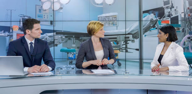 Journalists sitting with businesswoman Journalists taking live interview of businesswoman in television studio. anchor stock pictures, royalty-free photos & images