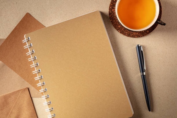 Journalling concept. Brown paper journal, top shot on a desk with a cup of tea and a pen stock photo