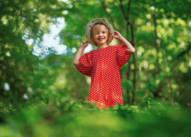 viaje en la naturaleza. pequeño pelo rubio y ojos azules chica en hierba alta verde, expresión sonriente. chica en lunares vestido rojo y sombrero de paja riendo en voz alta abriendo boca ancha en la naturaleza - gran inauguración fotografías e imágenes de stock