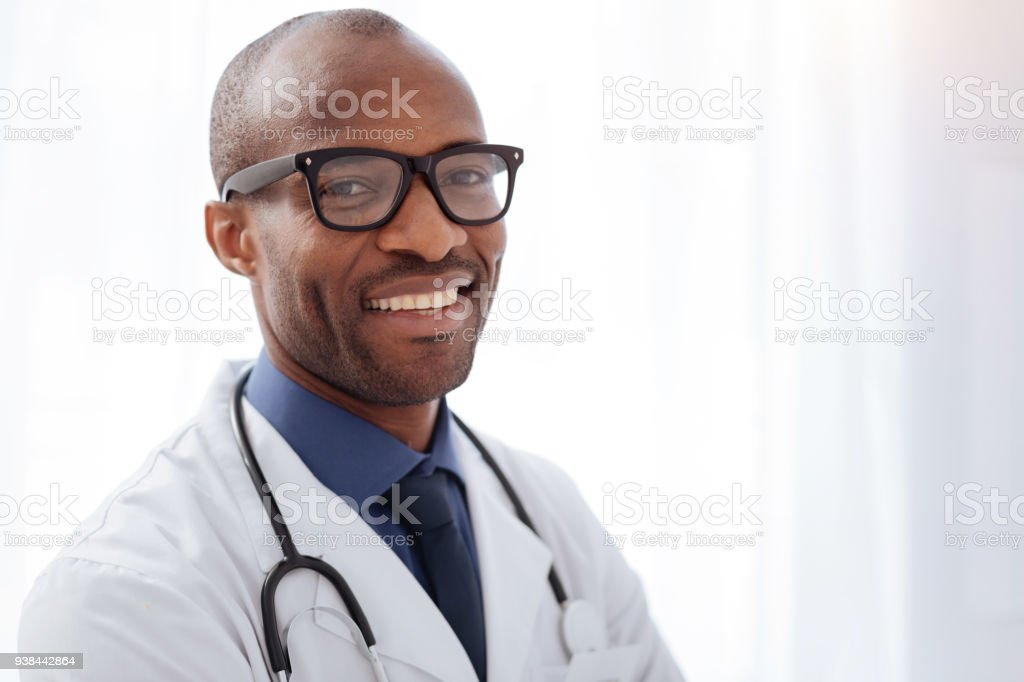 Jovial male doctor smiling to camera stock photo