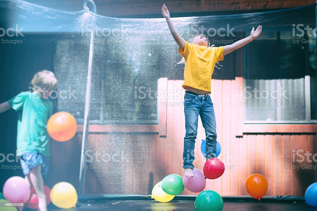 Joy, a young child throws her hands up in excitement stock photo