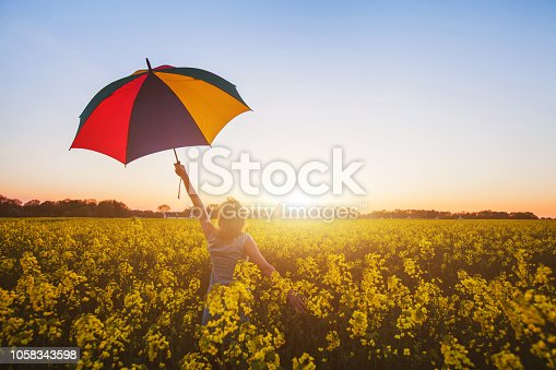 happy woman with colorful umbrella at sunset flower field, joy concept