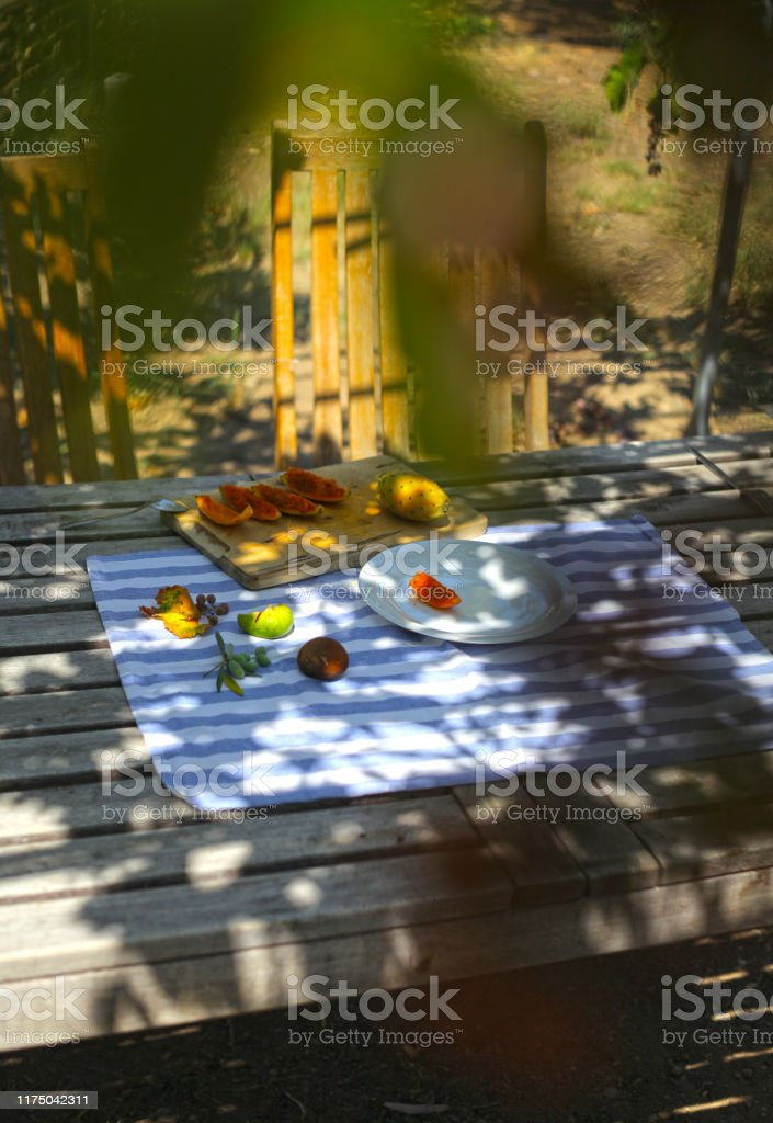 Lazy summer day with wooden table and different kind of fruits under...