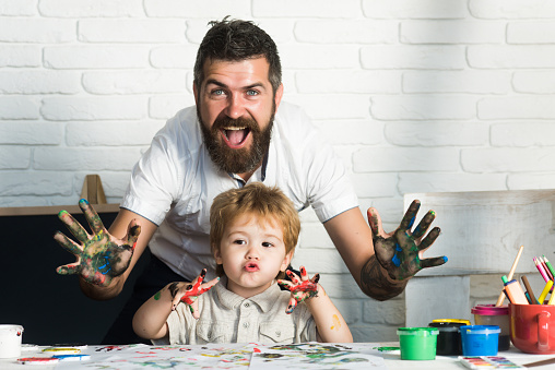 istock Joy family art, happy father and son show hands in bright colors, paint together picture, art for whole family, cheerful drawing teacher. Home education with parents. Happy childhood. Hands in paint 834754926