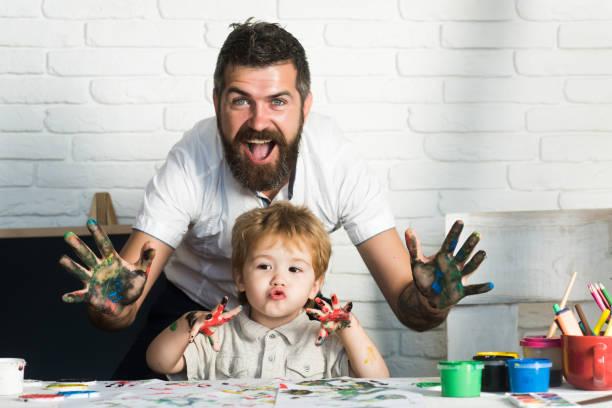 malen sie familie kunst freude, glückliche vater und sohn zeigen hände in leuchtenden farben gemeinsam bild, kunst für die ganze familie, fröhlich zeichenlehrer. bildung zu hause mit den eltern. glückliche kindheit. hände in farbe - papa humor stock-fotos und bilder