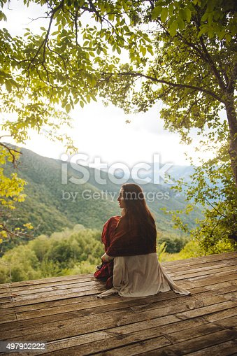 Pastel toned image of a young brunette on a trip to nature, enjoying the view on top of the mountain range. She is dressed in vintage hippie fashion, wearing oriental trousers and a poncho, sitting on the wooden terrace with a beautiful view over the canyon and the forest.