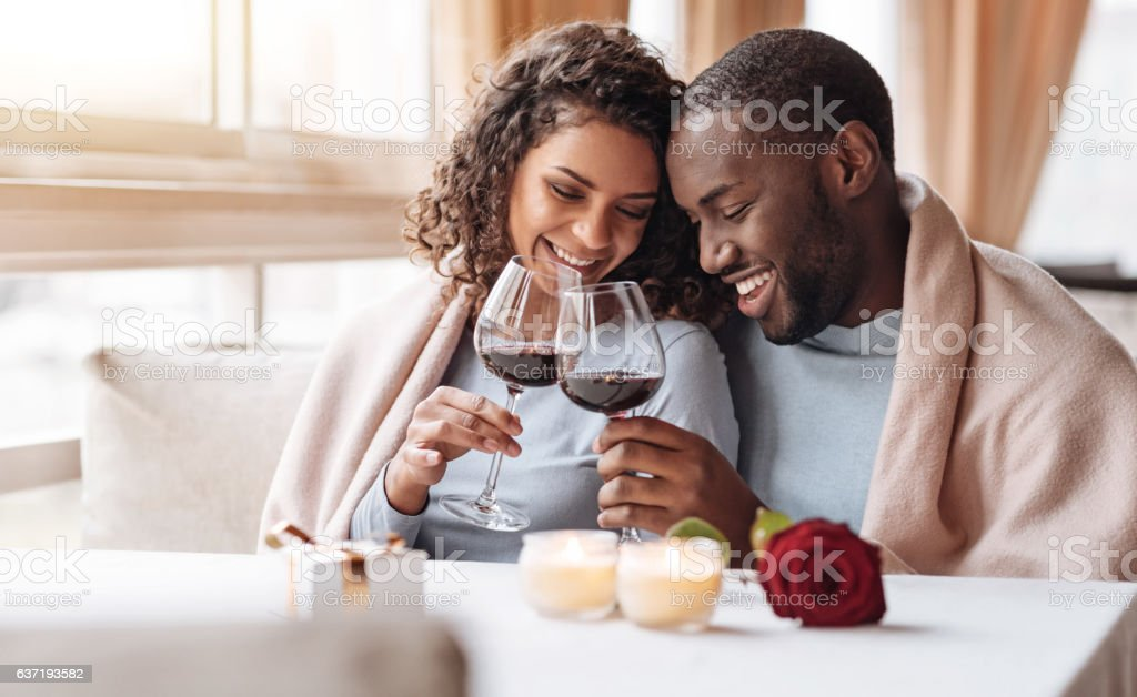 Joyful African American couple drinking wine in the restaurant stock photo