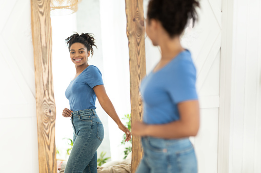 Successful Weight Loss. Joyful African American Girl After Slimming Smiling To Her Reflection In Mirror Standing At Home. Staying Fit, Dieting And Weight-Loss Concept. Selective Focus