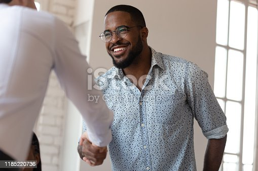 509032417 istock photo Joyful african american millennial worker shaking hands with colleague. 1185220736