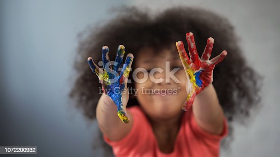 Joyful African female child having fun and showing painted palms into camera