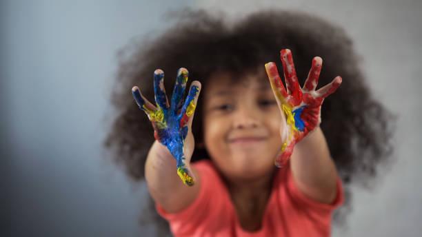 fröhliche afrikanische mädchen spaß und zeigt malte palmen in kamera - kindergarten workshop stock-fotos und bilder