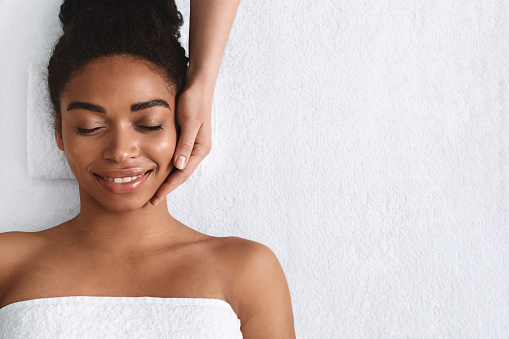 Joyful african girl having face massage at spa