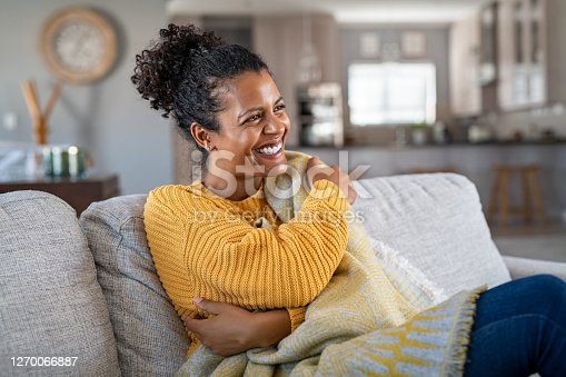 Beautiful black girl sitting on couch wrapped under blanket and laughing. Cheerful african american woman sensitive to the cold relaxing at home on sofa. Carefree and happy mid woman hugging self with warm blanket in winter.