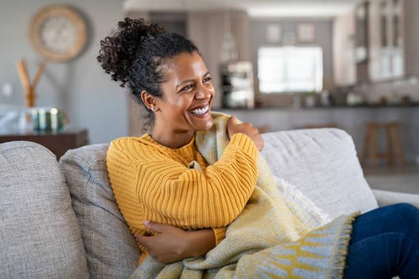 fröhliche afrikanische frau mit decke auf der couch lachen - 30 34 jahre stock-fotos und bilder