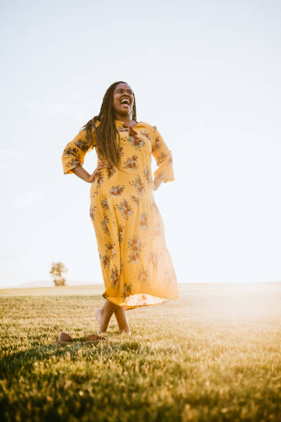 Joyful African Young Woman Outdoors A beautiful young adult African woman enjoys the beauty of the summer sun in an open field.  She stands laughing with her hands on her hips. Shot in Tacoma, Washington, USA. sun shining through dresses stock pictures, royalty-free photos & images