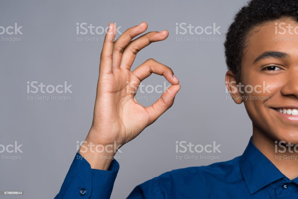 Joyful Afro American teen makes gesture ok. stock photo