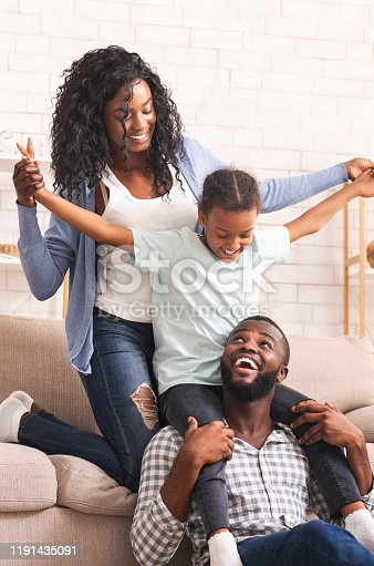 Family leisure activities. Joyful afro parents and their little daughter having fun together at home.
