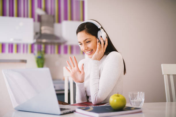 joyful and happy young woman is waving to a person she is studying with online while having her headset on. - woman chat video mobile phone foto e immagini stock