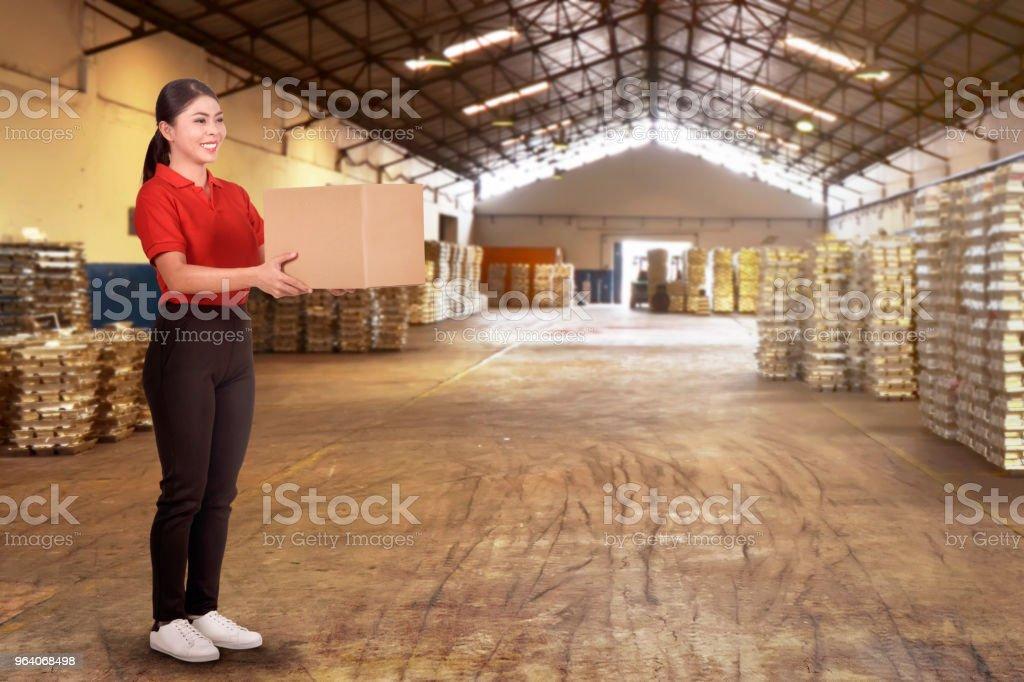 Joyful asian female courier holding cardboard box - Royalty-free Adult Stock Photo