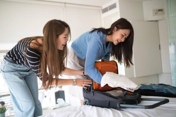 fröhliche asiatische freundinnen packen tasche für den urlaub - gepäck verpackung stock-fotos und bilder