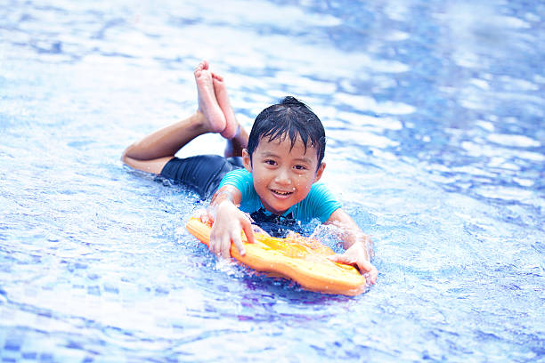 joyful asian kid at swimming pool - children play water park stock photos and pictures