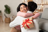 自宅でクリスマスプレゼントを受け取る夫を抱きしめる喜びのアジアの妻