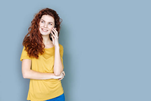 Joyful attractive woman having a phone conversation stock photo