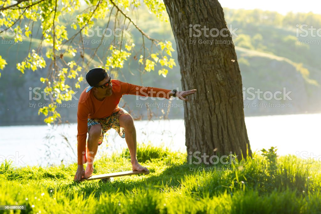 Joyful bearded man is training on the balance board royalty-free stock photo